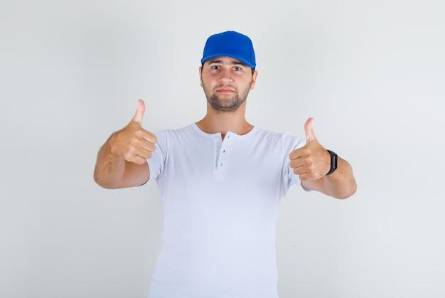 Młody mężczyzna w białej koszulce, niebieskiej czapce pokazującej kciuki do góry i pewnej siebie