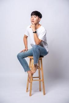 Młody mężczyzna w białej koszulce siedzi na wysokim krześle.