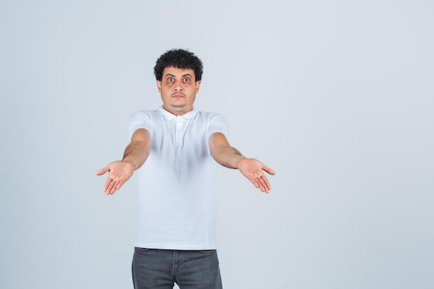 Młody mężczyzna w białej koszulce, spodniach rozkładających puste dłonie i patrzący zdezorientowany, widok z przodu.