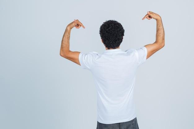 Młody mężczyzna w białej koszulce, spodniach wskazujących na siebie i patrzących pewnie, widok z tyłu.