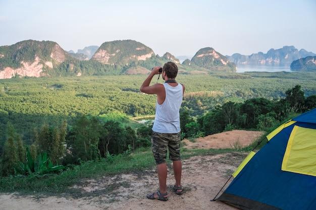 Młody mężczyzna w białej koszulce stoi na górze obok namiotu i spogląda w dal przez lornetkę na dziką przyrodę.