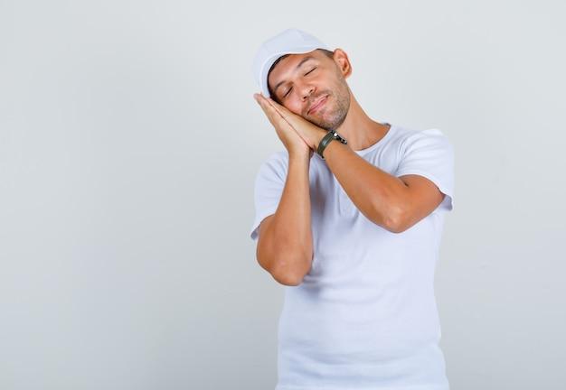 Młody mężczyzna w białej koszulce z czapką, oparty na dłoniach jako poduszce i wyglądający na zrelaksowanego, widok z przodu.