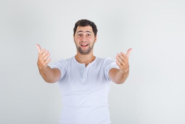 Młody mężczyzna w białej koszulce zaprasza do rąk i wygląda na szczęśliwego