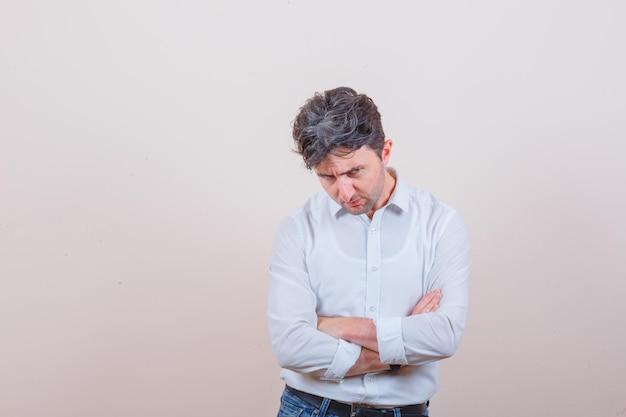 Młody mężczyzna w białej koszuli, dżinsach stoi ze skrzyżowanymi ramionami i wygląda ponuro