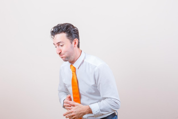 Młody mężczyzna w białej koszuli, dżinsach szuka czegoś komicznego