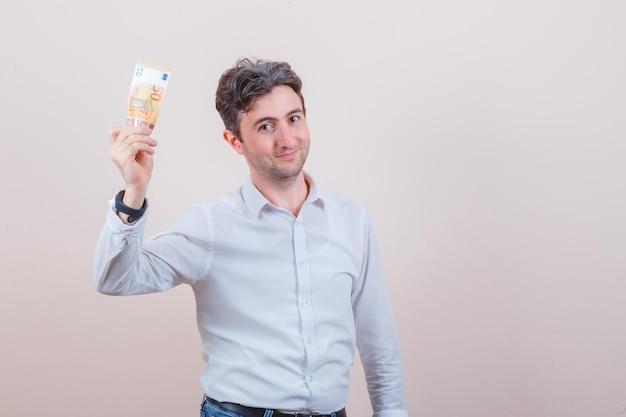 Młody mężczyzna w białej koszuli, dżinsach trzymających banknot euro i wyglądających na zadowolonych