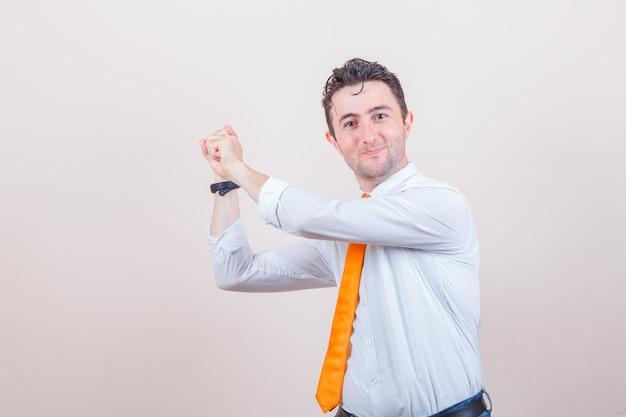 Młody mężczyzna w białej koszuli, dżinsy gestykulujące, jakby przygotowywał się do wypuszczenia strzały