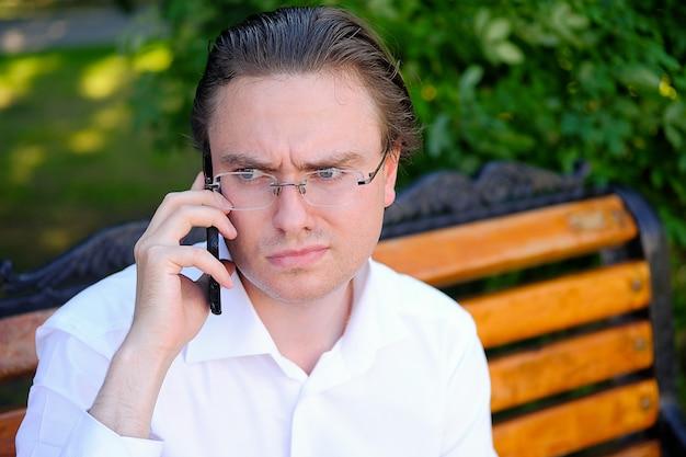 Młody mężczyzna w białej koszuli i okularach dzwoni na policję lub pogotowie.