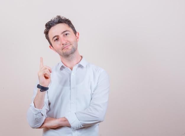 Młody mężczyzna w białej koszuli i patrzący optymistycznie