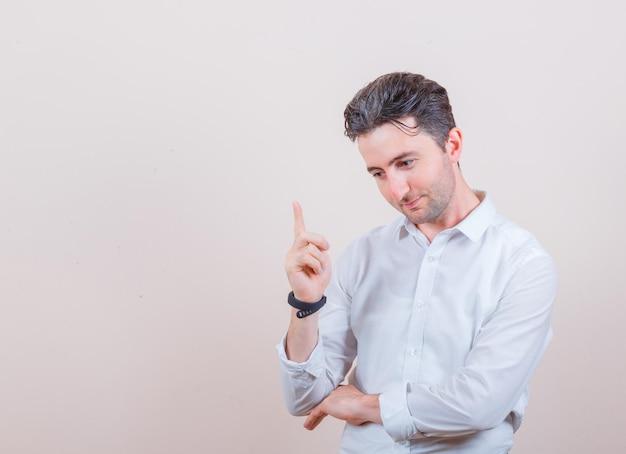 Młody mężczyzna w białej koszuli i zamyślony looking