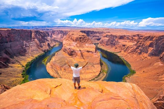 Młody mężczyzna w białej koszuli i zielonym kapeluszu na horseshoe bend i rzece kolorado w tle, arizona. stany zjednoczone