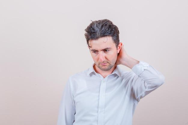 Młody mężczyzna w białej koszuli patrzący w dół z ręką na szyi i zamyślony