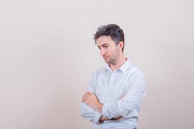 Młody mężczyzna w białej koszuli, patrzący w dół ze skrzyżowanymi rękami i zamyślony