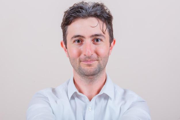 Młody mężczyzna w białej koszuli patrzący w kamerę i wyglądający na szczęśliwego