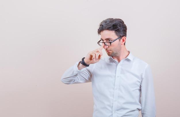 Młody mężczyzna w białej koszuli poprawia okulary i wygląda na zamyślonego