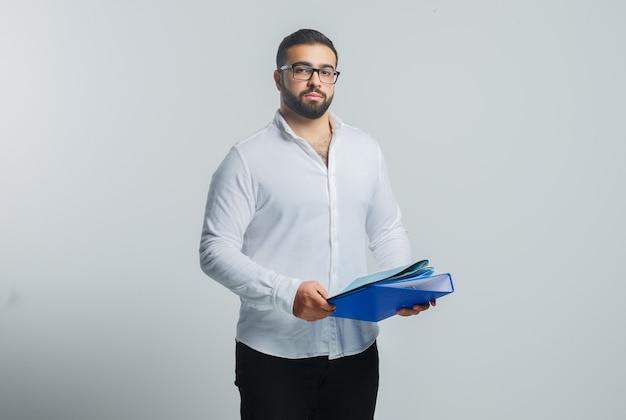 Młody mężczyzna w białej koszuli, spodniach, trzymając foldery i wyglądający pewnie
