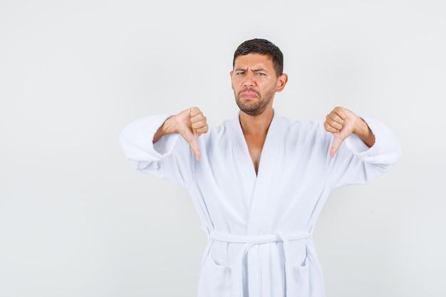 Młody mężczyzna w białym szlafroku pokazuje kciuk w dół i wygląda na niezadowolonego, widok z przodu.