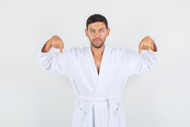 Młody mężczyzna w białym szlafroku skierowaną w dół i patrząc poważny, przedni widok.