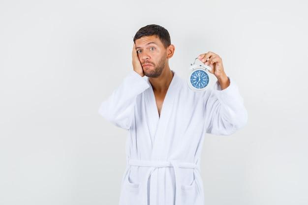 Młody mężczyzna w białym szlafroku trzymając budzik i patrząc bezradnie, widok z przodu.