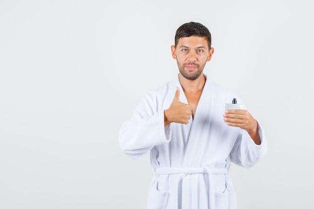 Młody mężczyzna w białym szlafroku trzymając perfumy z kciukiem do góry i patrząc pozytywnie, widok z przodu.