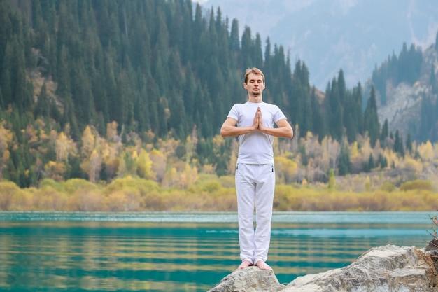 Młody mężczyzna w bieli ćwiczy jogę w górach. ustaw namaskar samasthiti.