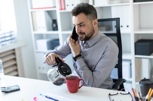 Młody mężczyzna w biurze siedzi przy stole, rozmawia przez telefon i nalewa kawę do filiżanki.