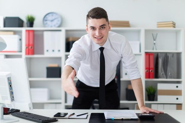 Młody mężczyzna w biurze wstaje i wyciąga rękę do przodu.