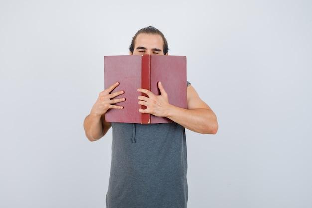 Młody mężczyzna w bluzie bez rękawów, trzymając otwartą książkę na twarzy i patrząc zaspany, widok z przodu.