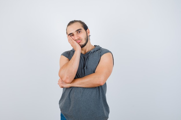 Młody mężczyzna w bluzie bez rękawów, trzymający rękę na policzku i wyglądający zamyślony, widok z przodu.