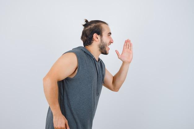 Młody mężczyzna w bluzie bez rękawów z kapturem, biegający i wyglądający wesoło, widok z przodu.