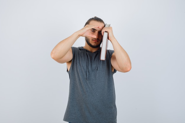 Młody mężczyzna w bluzie bez rękawów z książką na ramieniu, pokazując znak rozmiaru i patrząc poważnie, z przodu.