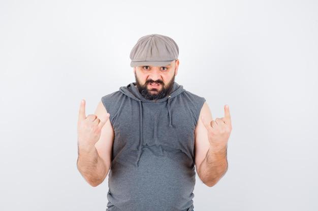 Młody mężczyzna w bluzie z kapturem bez rękawów, czapce pokazującej znak rocka i wyglądającym na szalonego, widok z przodu.