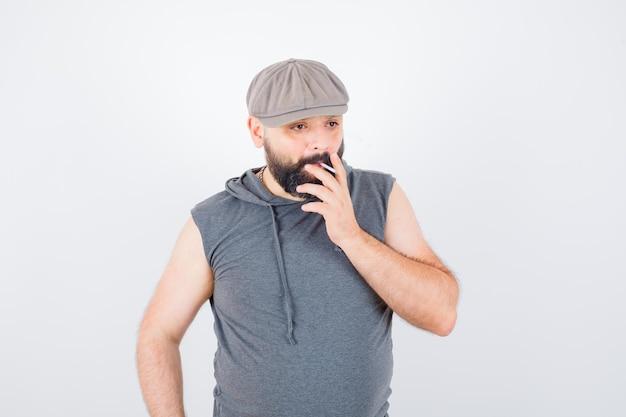 Młody mężczyzna w bluzie z kapturem bez rękawów, czapka paląca podczas pozowania i wyglądający pewnie, widok z przodu.