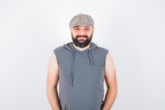 Młody mężczyzna w bluzie z kapturem bez rękawów, czapka patrząc na kamery i patrząc szczęśliwy, widok z przodu.