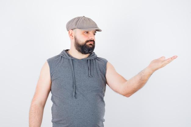 Młody mężczyzna w bluzie z kapturem bez rękawów, czapka podnosząca rękę w pytającej pozie i wyglądający pewnie, widok z przodu.