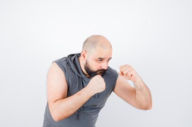 Młody mężczyzna w bluzie z kapturem bez rękawów stoi w pozie do walki i wygląda pewnie, widok z przodu.
