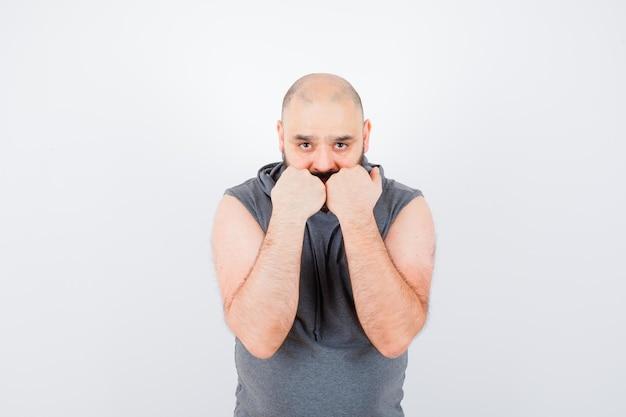 Młody mężczyzna w bluzie z kapturem bez rękawów stojący w pozie obronnej i patrzący pewnie, widok z przodu.