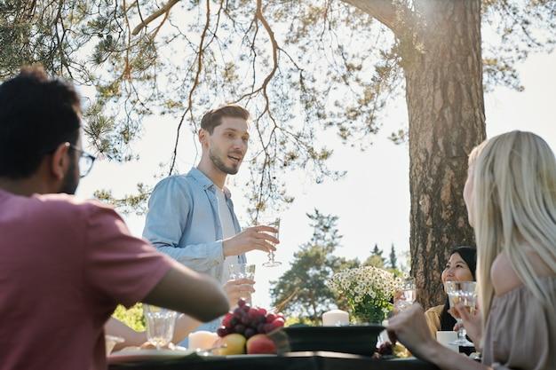 Młody mężczyzna w casualwear wypowiadający toast, stojąc przy serwowanym stole przed przyjaciółmi podczas kolacji pod sosną na świeżym powietrzu