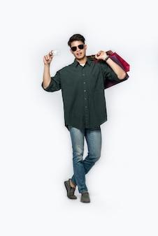 Młody mężczyzna w ciemnej koszuli i dżinsach niósł kilka toreb na zakupy z kartą kredytową