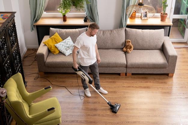 Młody mężczyzna w codziennej pracy wykonuje prace domowe podczas czyszczenia podłogi w salonie z odkurzaczem między fotelem a kanapą