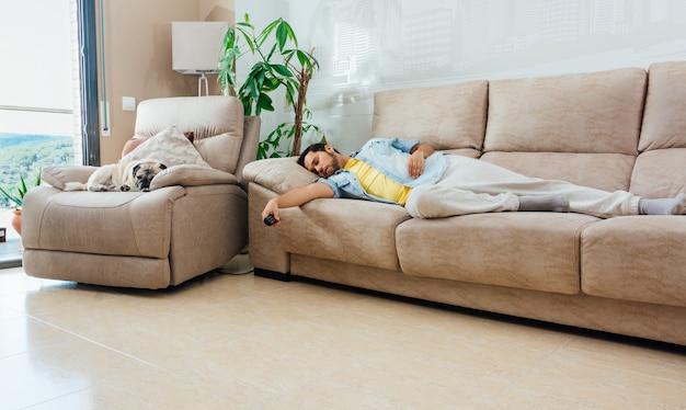Młody mężczyzna w codziennych ubraniach śpi na kanapie w domu z pilotem do telewizora w ręku