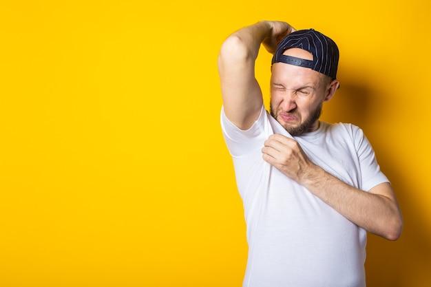 Młody mężczyzna w czapce i koszulce wącha jego pachy na żółtym tle.