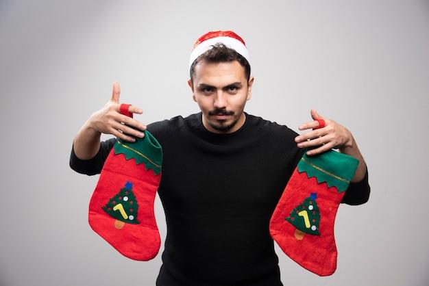Młody mężczyzna w czapce świętego mikołaja trzymający dwie świąteczne skarpety.