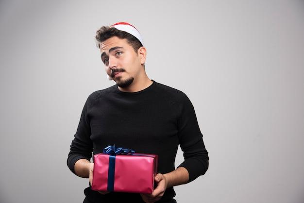 Młody mężczyzna w czapce świętego mikołaja trzymający prezent noworoczny.