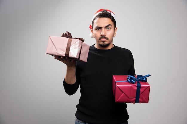 Młody mężczyzna w czapce świętego mikołaja trzymający prezenty noworoczne.