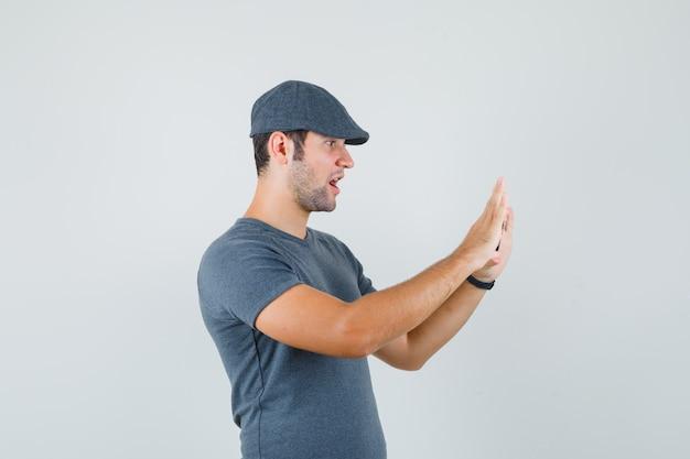 Młody mężczyzna w czapce t-shirt biorąc zdjęcie na telefon komórkowy i patrząc zdziwiony