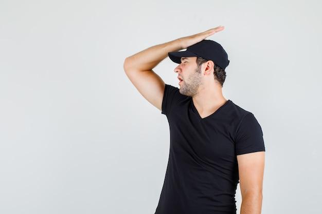 Młody mężczyzna w czarnej koszulce, czapce trzymającej rękę na głowie i patrząc z żalem
