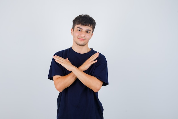 Młody mężczyzna w czarnej koszulce pokazuje gest odmowy i wygląda pewnie, widok z przodu.