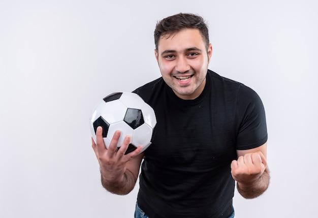 Młody mężczyzna w czarnej koszulce trzyma piłkę nożną bal l zaciskając pięść szczęśliwy i podekscytowany stojąc nad białą ścianą