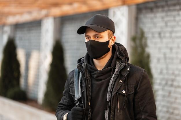 Młody mężczyzna w czarnej masce ochronnej i modnej czapce w czarnej stylowej bluzie z kapturem i zimowej kurtce z plecakiem spaceruje po mieście